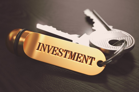 return on investment: Keys with Word Investment on Golden Label over Black Wooden Background. Closeup View, Selective Focus, 3D Render. Toned Image.