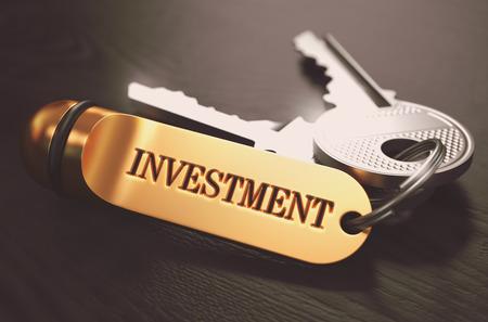 Touches avec Word investissement sur Golden étiquette sur fond de bois noir. Voir Gros plan, au point sélective, 3D Render. Image teintée. Banque d'images