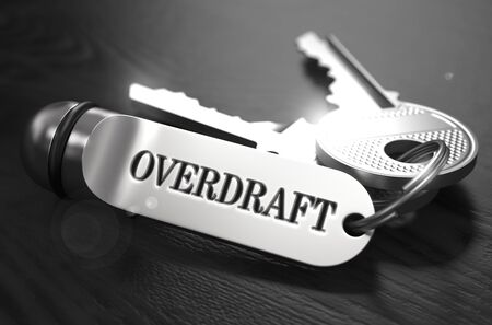 overdraft: Overdraft Concept. Keys with Keyring on Black Wooden Table. Closeup View, Selective Focus, 3D Render. Black and White Image. Stock Photo