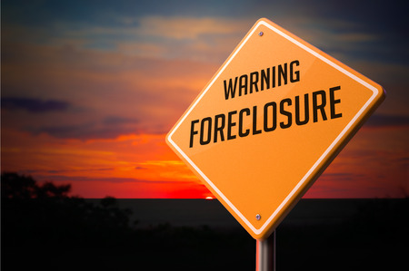 Foreclosure on Warning Road Sign on Sunset Sky Background. Stock Photo
