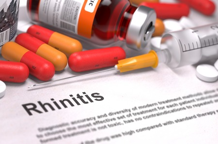 medicaments: Rhinitis - Printed Diagnosis with Blurred Text. On Background of Medicaments Composition - Red Pills, Injections and Syringe.