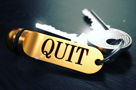 impasse: Keys and Golden Keyring with the Word Quit over Black Wooden Table with Blur Effect. Toned Image. Stock Photo