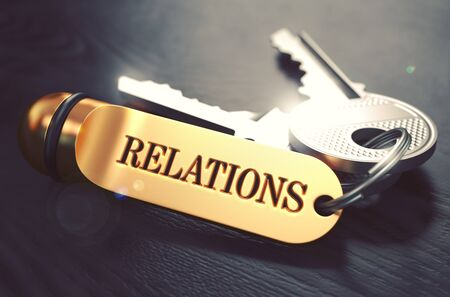 community recognition: Relations - Bunch of Keys with Text on Golden Keychain. Black Wooden Background. Closeup View with Selective Focus. 3D Illustration. Toned Image. Stock Photo