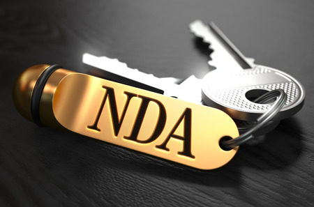 disclosure: Keys with Word NDA - Non Disclosure Agreement - on Golden Label over Black Wooden Background. Closeup View, Selective Focus, 3D Render.