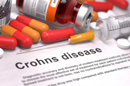 Crohns Disease - Printed Diagnosis with Blurred Text. On Background of Medicaments Composition - Red Pills, Injections and Syringe. Stock Photo