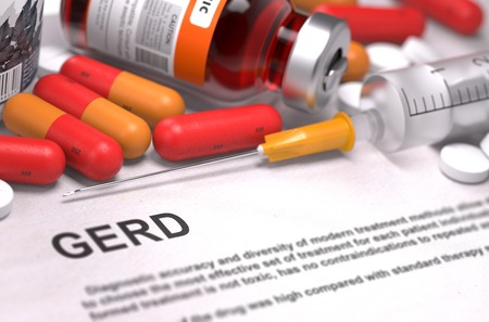 sphincter: GERD - Printed Diagnosis with Blurred Text. On Background of Medicaments Composition - Red Pills, Injections and Syringe. Stock Photo