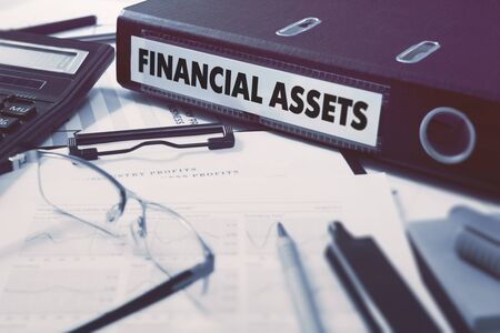 financial assets: Ring Binder with inscription Financial Assets on Background of Working Table with Office Supplies, Glasses, Reports. Toned Illustration. Business Concept on Blured Background.