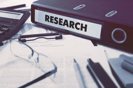 metodo cientifico: Carpeta de anillas con la inscripción de Investigación en el fondo de la Mesa de Trabajo con Material de Oficina, Gafas, Informes. Ilustración virada. Concepto de negocio en el fondo borroso.