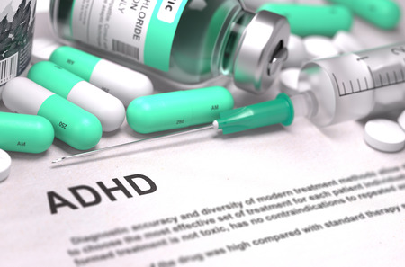 ADHD - Printed Diagnosis with Blurred Text. On Background of Medicaments Composition - Mint Green Pills, Injections and Syringe. Stock Photo