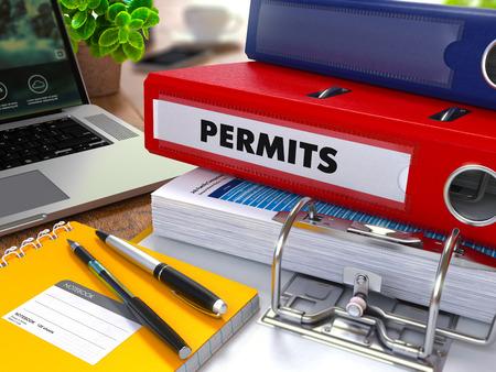 Red Ring Binder avec inscription sur les licences sur fond de la Table de travail avec les fournitures de bureau, ordinateur portable, Rapports. Illustration Virage. Concept sur fond flou.