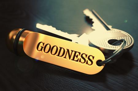 bondad: Teclas y oro llavero con la Bondad Palabra sobre tabla de madera Negro con efecto de desenfoque.
