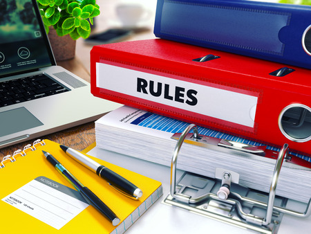 rigor: Rules - Red Ring Binder on Office Desktop with Office Supplies and Modern Laptop.