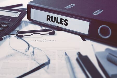 injunction: Office folder with inscription Rules on Office Desktop with Office Supplies. Business Concept on Blurred Background. Toned Image. Stock Photo