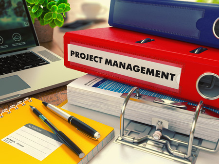 monitoreo: Carpeta roja de la oficina con la inscripción en la Oficina de Gestión de Proyectos de escritorio con Material de oficina y portátil moderno. Concepto de negocio en el fondo borroso. Imagen virada.