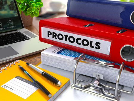 protocols: Red Ring Binder with Inscription Protocols on Background of Working Table with Office Supplies, Laptop, Reports. Toned Illustration. Business Concept on Blurred Background.