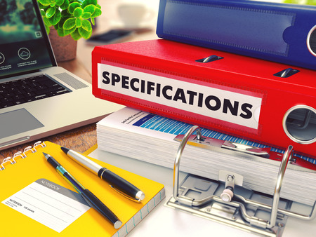 specifications: Specifications - Red Office Folder on Background of Working Table with Stationery, Laptop and Reports. Business Concept on Blurred Background. Toned Image.