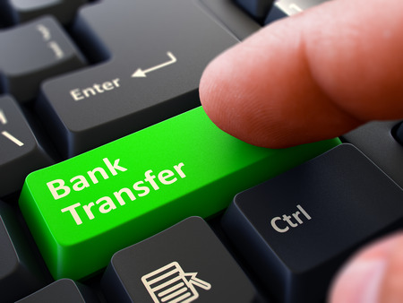 bank overschrijving: Bank Transfer Green Button - Finger Pushing Button of Black Computer Keyboard. Blurred Background. Closeup View.