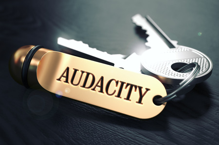 positiveness: Keys with Word Audacity on Golden Label over Black Wooden Background. Closeup View, Selective Focus, 3D Render. Toned Image. Stock Photo