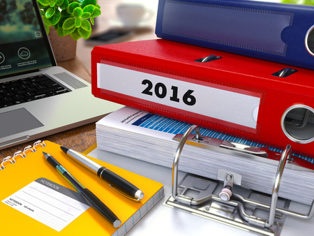 initiatives: Red Ring Binder with Inscription 2016 on Background of Working Table  Stock Photo