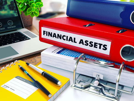 financial assets: Financial Assets - Red Ring Binder on Office Desktop with Office Supplies and Modern Laptop. Business Concept on Blurred Background. Toned Illustration. Stock Photo