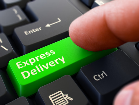 Finger Presses Green Button Express Delivery on Black Keyboard Background. Closeup View. Selective Focus. Stock Photo