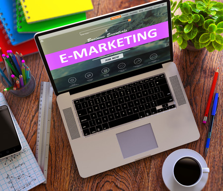emarketing: E-Marketing Concept. Modern Laptop and Different Office Supply on Wooden Desktop background.