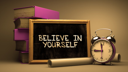 beliefs: Believe in Yourself Handwritten on Chalkboard. Time Concept. Composition with Chalkboard and Stack of Books, Alarm Clock and Scrolls on Blurred Background. Toned Image. Stock Photo