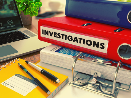 detective: Red Office Folder with Inscription Investigations on Office Desktop with Office Supplies and Modern Laptop. Business Concept on Blurred Background. Toned Image. Stock Photo