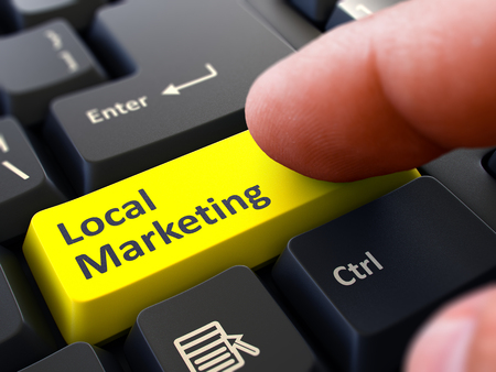 grassroots: Local Marketing Button. Male Finger Clicks on Yellow Button on Black Keyboard. Closeup View. Blurred Background.