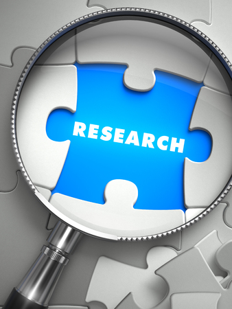 place of research: Research - Word on the Place of Missing Puzzle Piece through Magnifier. Selective Focus.
