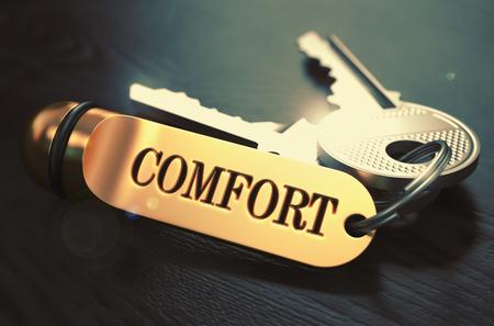 competitividad: Confort - Manojo de llaves con el texto en el llavero de oro. Fondo De Madera Negro. Primer punto de vista con enfoque selectivo. Ilustraci�n 3D. Imagen virada.