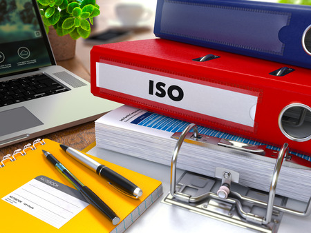 standardization: Red Ring Binder with Inscription ISO on Background of Working Table with Office Supplies, Laptop, Reports. Toned Illustration. Business Concept on Blurred Background.