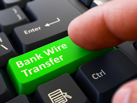 One Finger Presses Green Button Bank Wire Transfer on Black Computer Keyboard. Closeup View. Selective Focus. 스톡 콘텐츠