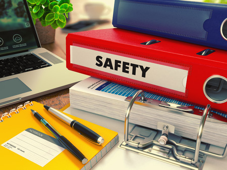health risk: Red Office Folder with Inscription Safety on Office Desktop with Office Supplies and Modern Laptop. Business Concept on Blurred Background. Toned Image.