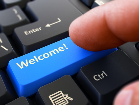 civility: Welcome Button. Male Finger Clicks on Blue Button on Black Keyboard. Closeup View. Blurred Background.