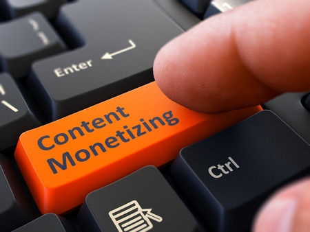 monetizing: Content Monetizing Button. Male Finger Clicks on Orange Button on Black Keyboard. Closeup View. Blurred Background.