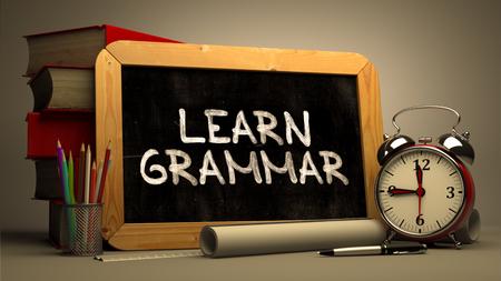 動機付けの引用 - 手書き黒板 - 文法を学ぶ。黒板と書籍、目覚まし時計、背景をぼかした写真のロール紙のスタック構成。トーンのイメージ。