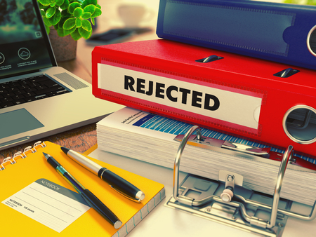 deflect: Red Office Folder with Inscription Rejected on Office Desktop with Office Supplies and Modern Laptop. Business Concept on Blurred Background. Toned Image.