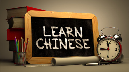 erudition: Learn Chinese - Chalkboard with Hand Drawn Text, Stack of Books, Alarm Clock and Rolls of Paper on Blurred Background. Motivational Quote. Toned Image.