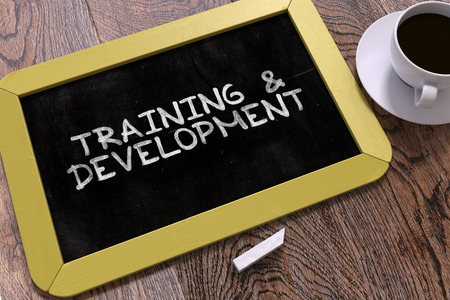 td: Hand Drawn Training and Development Concept  on Small Yellow Chalkboard. Business Background. Top View. Stock Photo