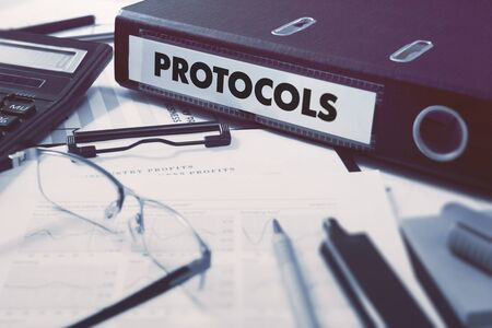 protocols: Ring Binder with inscription Protocols on Background of Working Table with Office Supplies, Glasses, Reports. Toned Illustration. Business Concept on Blurred Background. Stock Photo