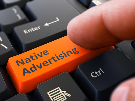 Native Advertising Button. Male Finger Clicks on Orange Button on Black Keyboard. Closeup View. Blurred Background. Imagens