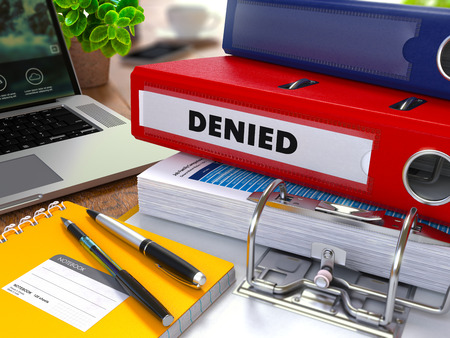 disclaim: Red Ring Binder with Inscription Denied on Background of Working Table with Office Supplies, Laptop, Reports. Toned Illustration. Business Concept on Blurred Background.
