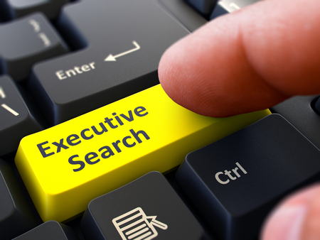executive search: Executive Search Yellow Button - Finger Pushing Button of Black Computer Keyboard. Blurred Background. Closeup View. Stock Photo