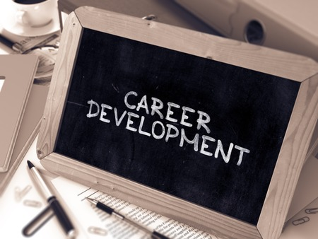 career development: Career Development Handwritten by white Chalk on a Blackboard. Composition with Small Chalkboard on Background of Working Table with Office Folders, Stationery, Reports. Blurred, Toned Image.