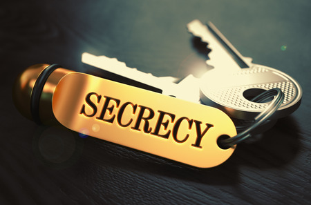 secrecy: Keys and Golden Keyring with the Word Secrecy over Black Wooden Table with Blur Effect. Toned Image. Stock Photo