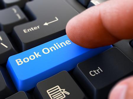 Finger drückt blaue Knopf-Buch online auf schwarzem Tastatur-Hintergrund. Nahaufnahme. Selektiver Fokus Lizenzfreie Bilder