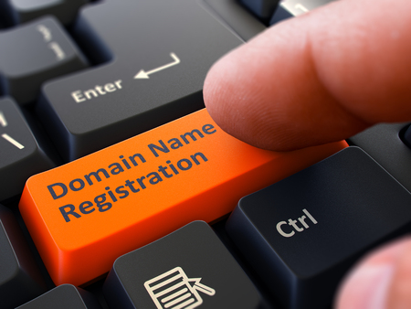 hosting: Finger Presses Orange Button  Domain Name Registration on Black Keyboard Background. Closeup View. Selective Focus.