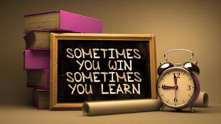 Parfois vous gagnez, parfois vous apprenez - Citation de motivation sur Chalkboard avec le texte Hand Drawn, pile de livres, de réveil et de rouleaux de papier sur fond flou. Image teintée. Banque d'images