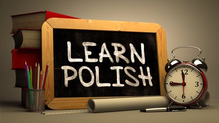 fluent: Learn Polish - Chalkboard with Hand Drawn Text, Stack of Books, Alarm Clock and Rolls of Paper on Blurred Background. Toned Image.